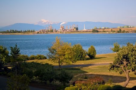 An oil refinery and tanks on the Puget Sound at Anacortes Island, Washington, with Mount Baker in the distance and a park in the foreground. 版權商用圖片 - 5200939