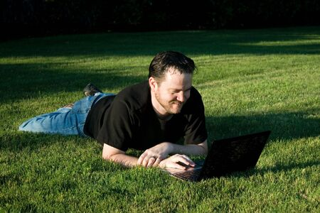 A young Caucasian man works with his laptop computer on the lush green grass.