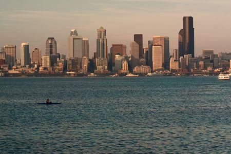 puget sound: Seattle, Washington skyline al tramonto, con Puget Sound in primo piano, con un kayaker e traghetti.