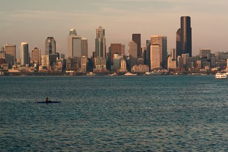 puget: The Seattle, Washington skyline at sunset with Puget Sound in the foreground, with a kayaker and ferry boats. Stock Photo