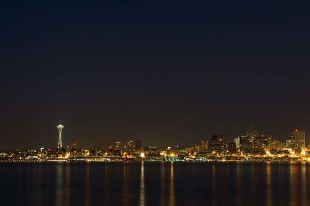 puget: The Seattle, Washington skyline at night with Puget Sound in the foreground, with lots of sky copyspace. Stock Photo