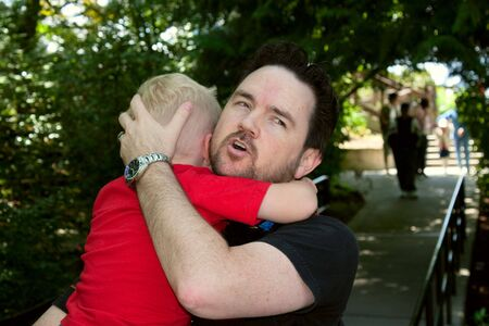 A loving father comforts his crying son outdoors on a summer day. Stock Photo