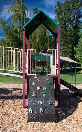 bark mulch: A playground set containins slides, jungle gyms, brigdes and a climbing wall.