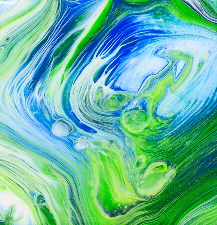 A blue and green tree ring pour acrylic flow art painting.