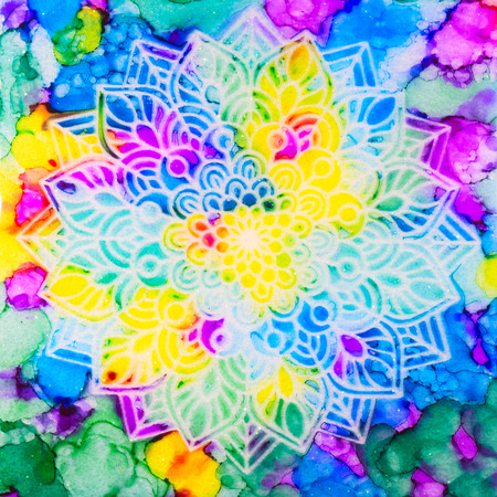 A stenciled mandala over a metallic pearl sublayer with brilliant alcohol ink rainbow design. Stock Photo