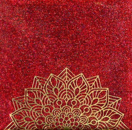 A gold mandala half circle over red holographic glitter background. Foto de archivo