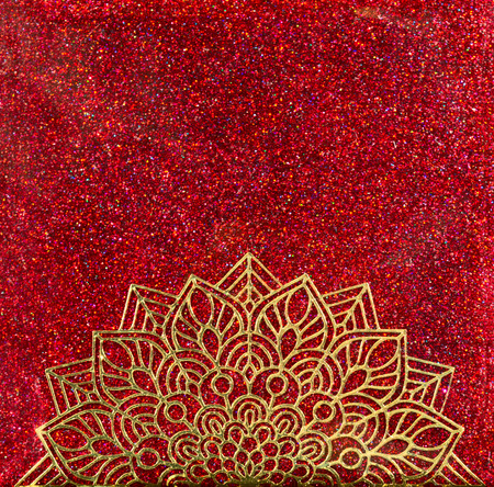 A gold mandala half circle over red holographic glitter background. 写真素材