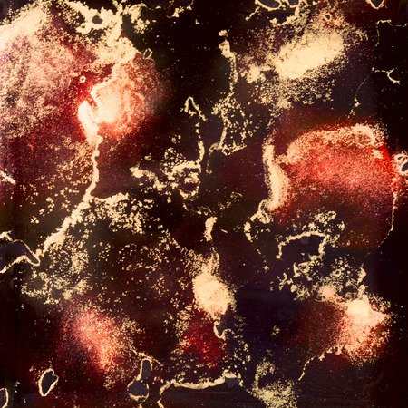 Red and black shades and gold dust in alcohol inks.