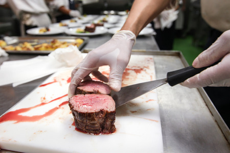 keuken restaurant: Chef in hotel or restaurant kitchen cooking, he is picking beef steak put on plate for dinner