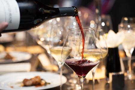 ウェイトレスはテーブルでレストランのガラスに赤ワインを注ぐ