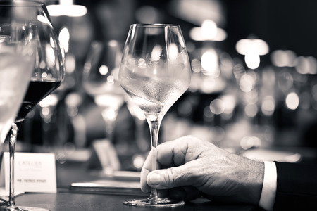 black and white of white wine on hand with dinner on restaurant