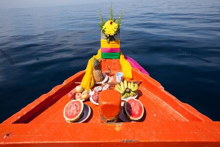 trawl: Head of Thai local fisherman boats, decorated with long fabric strips in various color and fruits respect to the faith Stock Photo