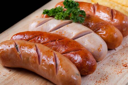 black block: Grilled sausage with chili powder and french fries and parsley on top of sausage on wooden block on black table. Foto de archivo