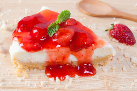 Close up strawberry cake on wooden plate on wood table.
