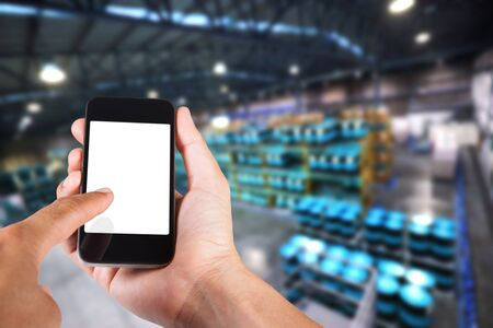 industry background: Person using smartphone white screen holder on hand with blurry background of industrial factory.