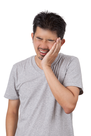 The sick man standing on white background and put his hand on his cheek with painful is showing of his face.