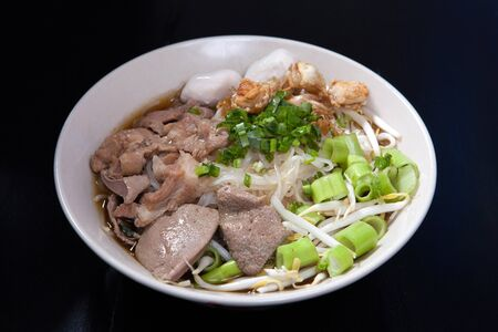 Rice noodle soup with Stewed pork with thai style on black wood table.