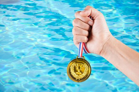 champ: handful of asian man holding gold medal with blurry background of swimming pool.