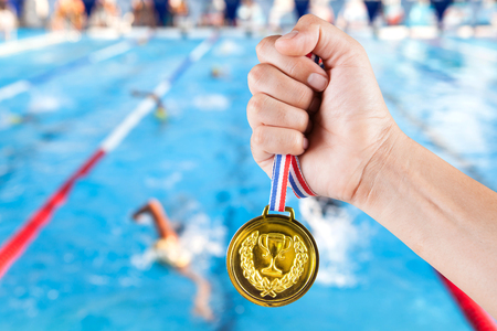 handful of asian man holding gold medal with blurry background of swimming pool and swimming competition.
