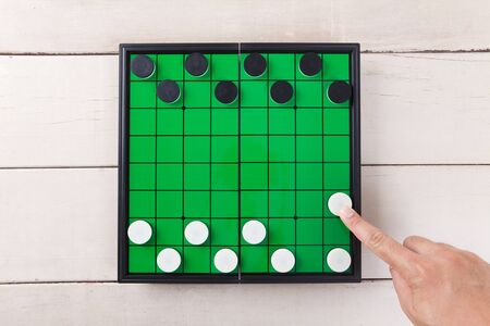 checker: Start checker game on green board view from above on wood table. Stock Photo