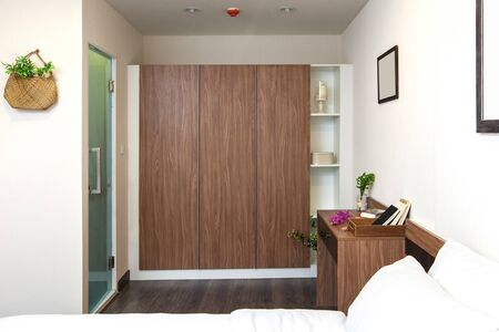 ceiling: Wardrobe built in and desk wooden on the bedroom with toilet in side in condominium.