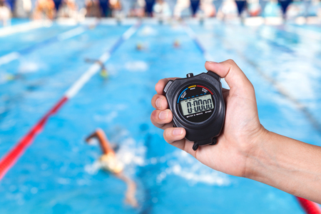 Stopwatch holding on hand with competitions of swimming background. Stock Photo