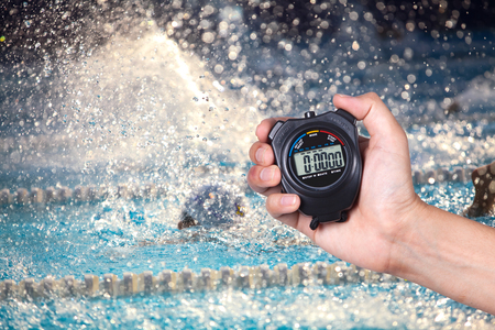 Stopwatch holding on hand with competitions of swimming background. Stockfoto