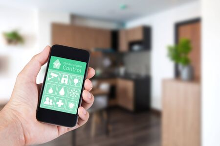 hight tech: Hand using smartphone to smart home app on mobile for remote control everything in home by wifi network. Stock Photo