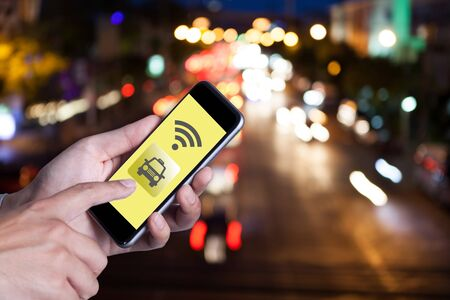 mobile app: Hand of man using smartphone call taxi by application smartphone and wifi networking with bokeh background of car on the road. Stock Photo