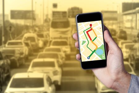 map pin: Hand of man using map on smartphone application with traffic jam background.