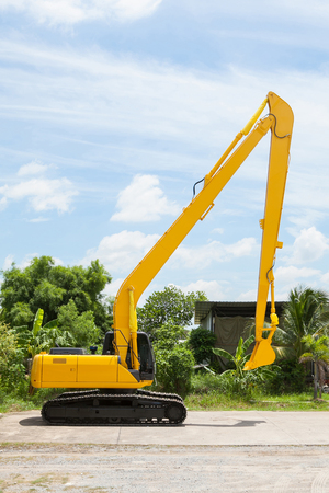 Hydraulic Yellow Excavator side view on outdoor location.
