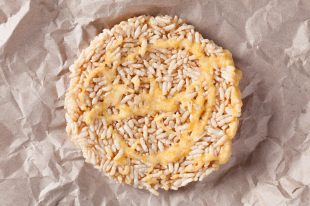 Nang Let is a name of rice cake round and flat sweetmeat is a dessert in Thailand, Put on crumpled brown paper background.