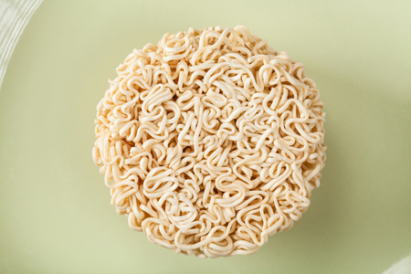 Close up Raw Instant noodles isolated on a green plate with space for copy.