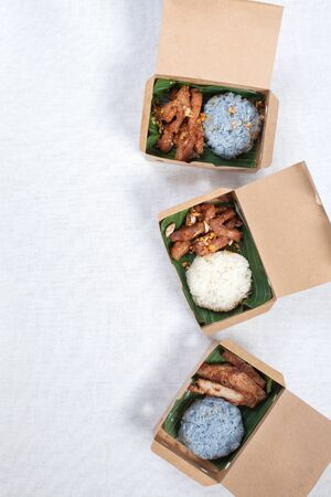 Sticky rice with grilled pork and fried pork put in a brown paper box, put on a white tablecloth, food box, Thai food. Stok Fotoğraf - 132111916