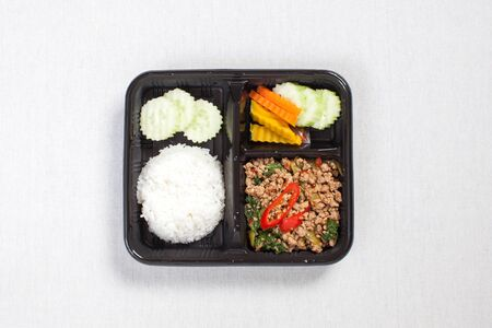 Basil fried rice with minced pork, put in a black plastic box, put on a white tablecloth, food box, Spicy fried pork with basil leaves, Thai food. 写真素材