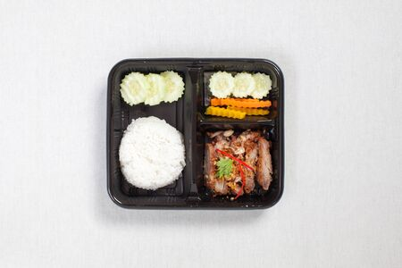 Fried Pork with Garlic and Pepper and rice put in black plastic box, put on a white tablecloth, food box, Thai food. 写真素材