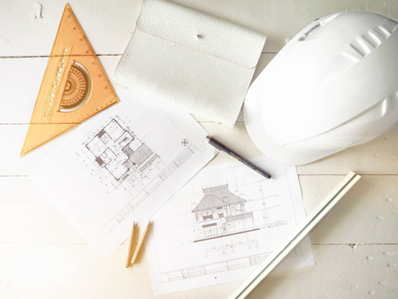 Engineer stationerys include pencil,pen,paper,notebook and construction helmet on white wood table.