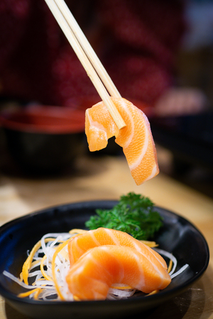 Chopsticks tong fresh salmon sashimi (japanese food) put on sliced radish and carrot.