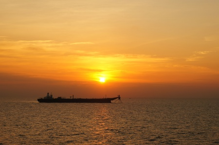 barge: Large oil tanker anchored in the middle of sea in the evening Stock Photo