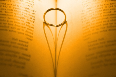 word of god: Ring and heart shaped shadow over a book - Golden Tone