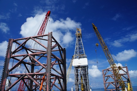 oilfield: Jack Up Offshore Drilling Rig With Rig Cranes on Sunny Day in The Middle of Ocean Stock Photo