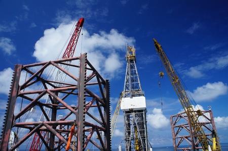 yacimiento petrolero: Jack Up torre de perforación costa afuera con grúas del equipo de perforación en un día soleado en el centro del Océano