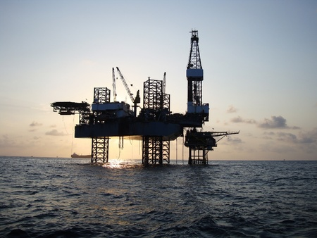 drilling well: Silhouette of Offshore Jack Up Rig in The Middle of The Sea at Sunset Time Stock Photo