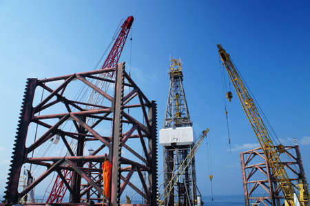 Jack Up Offshore Drilling Rig With Rig Cranes on Sunny Day in The Middle of Ocean               photo