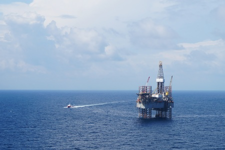 drilling rig: Jack up drilling rig and crew boat in the middle of the sea
