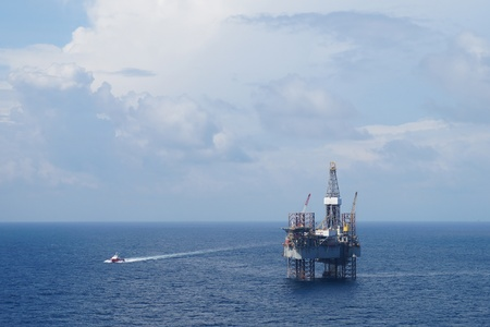 oil platforms: Offshore Drilling Platform (Jack up drilling rig) and crew boat in the middle of the coean