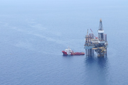 Offshore Jack Up Drilling Rig and Supply Boat In The Middle Of The Ocean photo