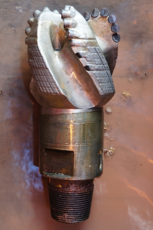 Damaged PDC drilling bit on the rig floor photo