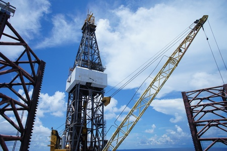 driller: Jack Up Oil Rig (Drilling Rig) and Rig Crane Working In The Middle Of The Ocean Stock Photo