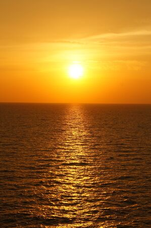 billow: Yellow Sun Set in The Middle of The Ocean Stock Photo